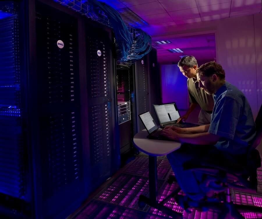 Desenvolvedores trabalhando próximo a um servidor com muitos cabos.