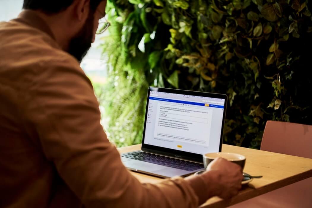 Homem trabalhando no notebook, com uma xícara de café ao lado.